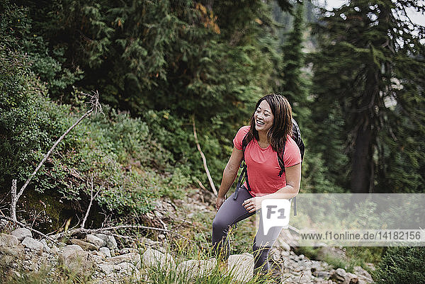 Happy young woman hiking in woods