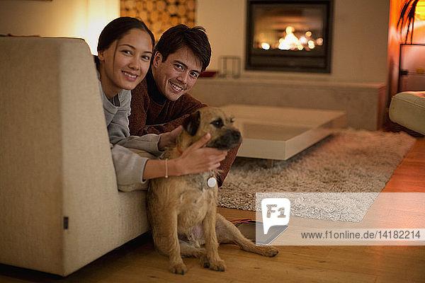 Portrait glückliches Paar mit Hund im Wohnzimmer