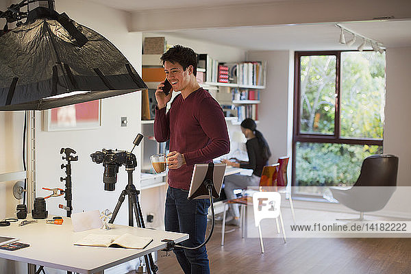 Male photographer working in studio  taking coffee break
