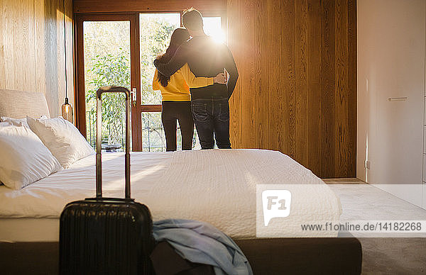 Couple with suitcase hugging in bedroom