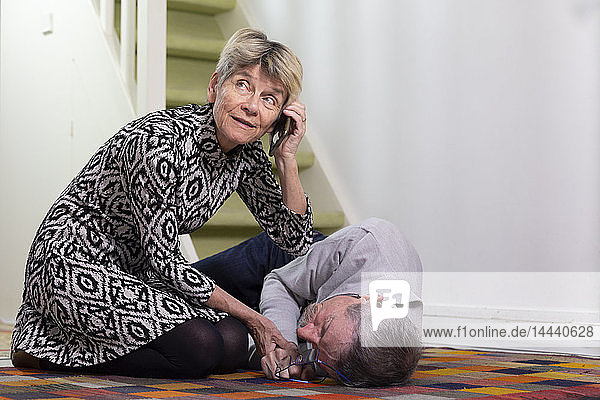 An elderly woman helping an elderly man who has fallen down stairs.