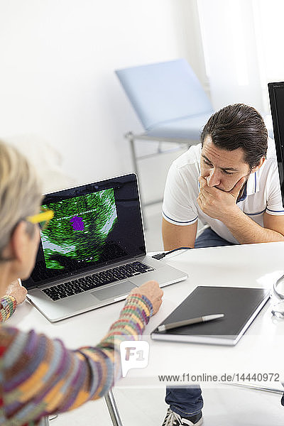 Man consulting a female doctor for prostate ultrasound examination.