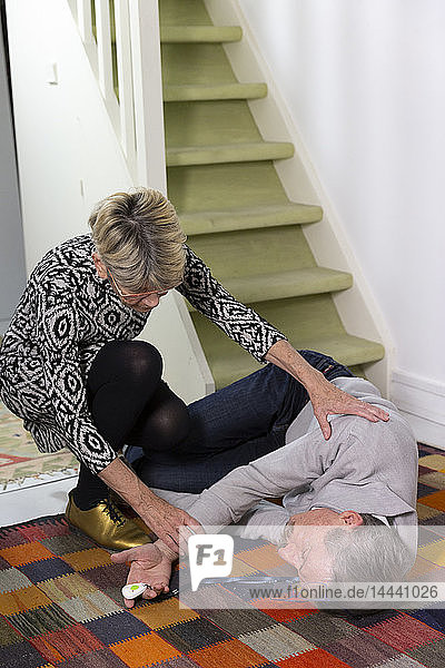 An elderly woman helping an elderly man who has fallen down stairs.