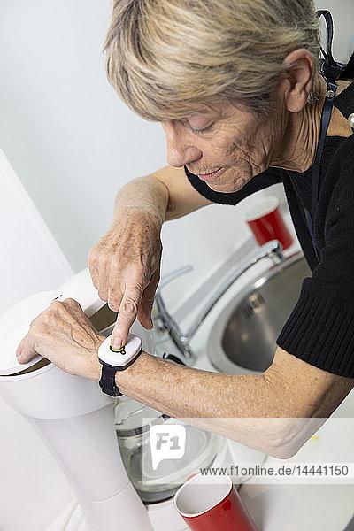 Elderly woman with a medical alert system around her wrist.