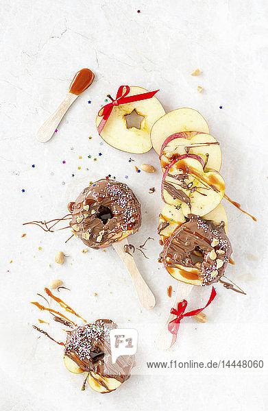 Karamellisierte Apfelscheiben am Stiel mit Schokoglasur  Nüssen und Zuckerstreuseln