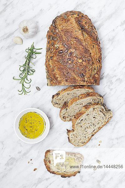 Frisch gebackener Brotlaib mit Samen und Schälchen Olivenöl