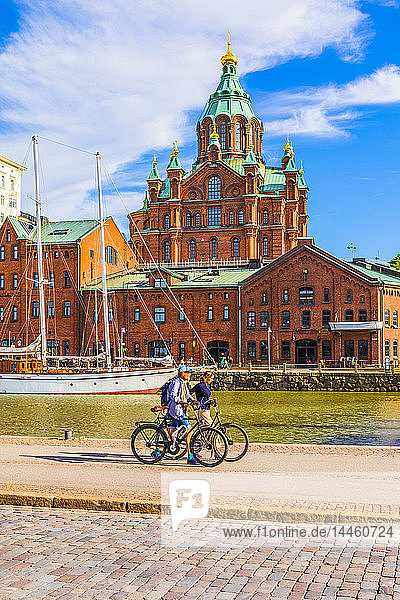 Uspenski Cathedral and cyclists by harbor in Helsinki  Finland