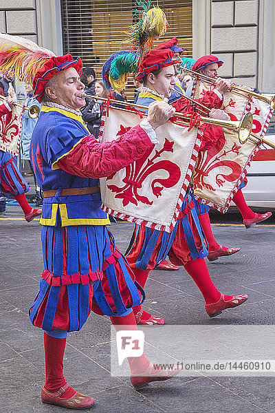 Marching men in costume playing fanfare trumpets during Scoppio del Carro festival in Florence  Tuscany  Italy