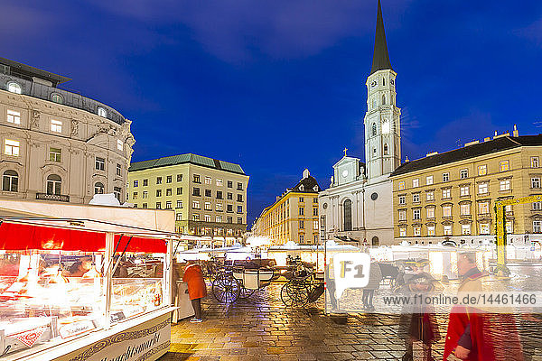 View of Christmas Markets stalls and St. Michael Catholic Church in Michaelerplatz at dusk  Vienna  Austria