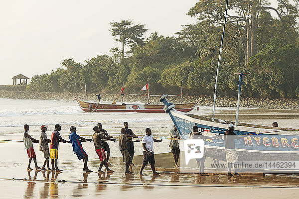 Men pulling boat out to sea  Busua  Ghana