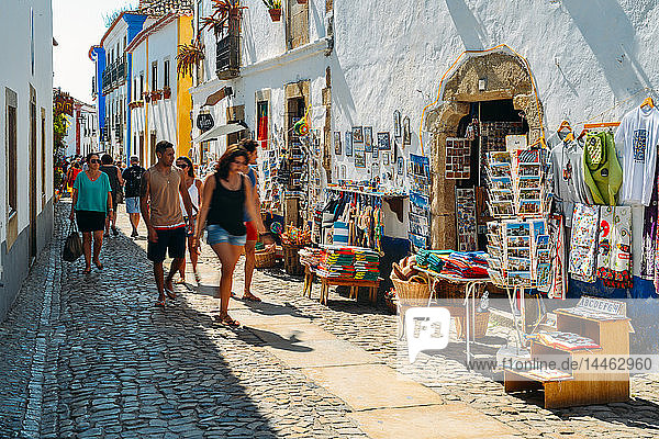 Tourists and shops in the typical alleys of the ancient fortified village of Obidos  Oeste Leiria District  Portugal