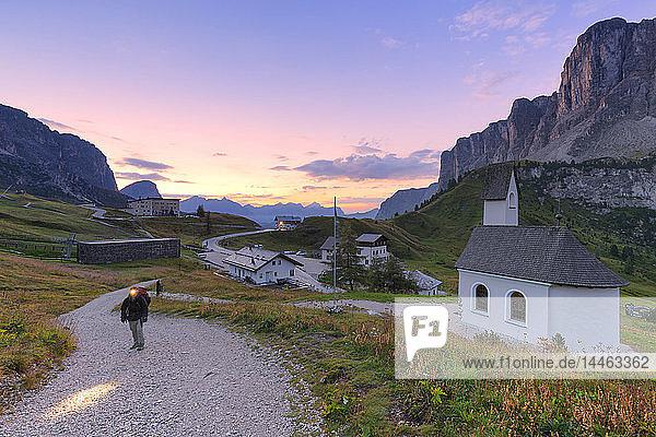 Hiker walks on a track during sunrise  Gardena Pass  Gardena Valley  South Tyrol  Dolomites  Italy