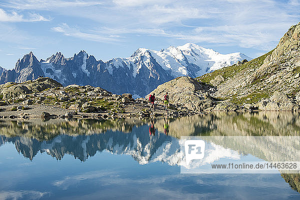 Hikers and the summit of Mont Blanc reflected in Lac Blanc on the Tour du Mont Blanc trekking route in the French Alps  Haute Savoie  Auvergne-Rhone-Alpes  France