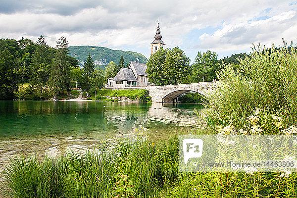 The bridge and church in the lakeside village of Ribcev Laz  Lake Bohinj  Slovenia