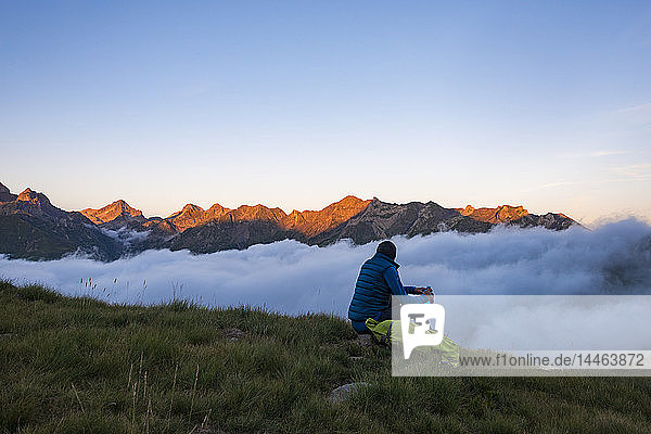 A hiker watches the sunset on the Pyrenees and a cloud inversion near Refuge Pombie along the GR10 trekking route  Pyrenees Atlantiques  France