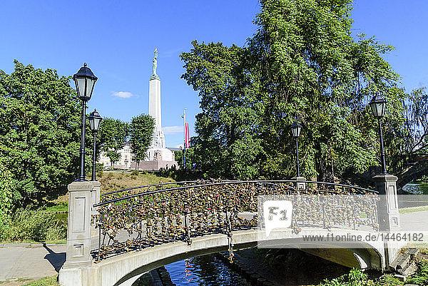 Freedom Monument and bridge with love lockets  Bastejkalna Parks  Riga  Latvia