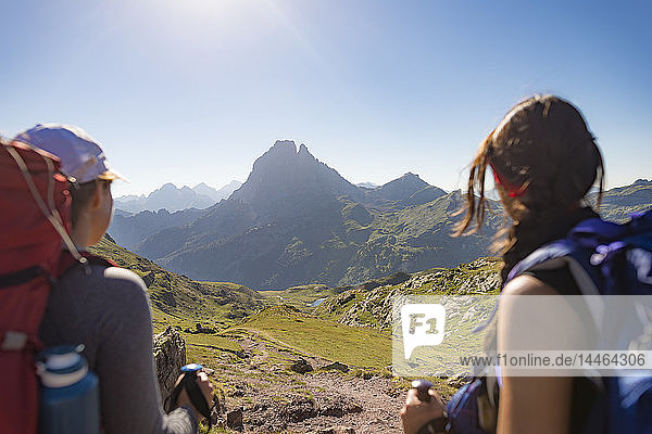 Walkers admire the view of Pic du Midi d'Ossau from the top of Col d'Ayous on the GR10 trekking route  Pyrenees Atlantiques  France