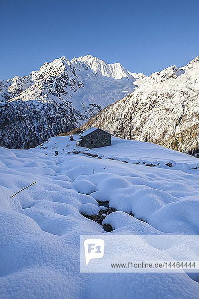 Stone hut at the foot of the snowy Monte Vazzeda  Alpe dell'Oro  Valmalenco  Valtellina  Sondrio province  Lombardy  Italy