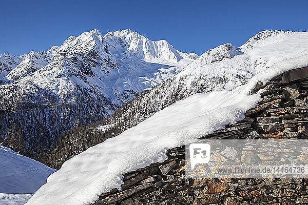 Stone hut covered with snow with Monte Disgrazia on background  Alpe dell'Oro  Valmalenco  Valtellina  Lombardy  Italy
