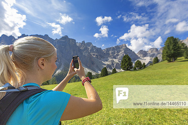 Girl takes a photo with a smartphone  Longiaru  Badia Valley  South Tyrol  Dolomites  Italy