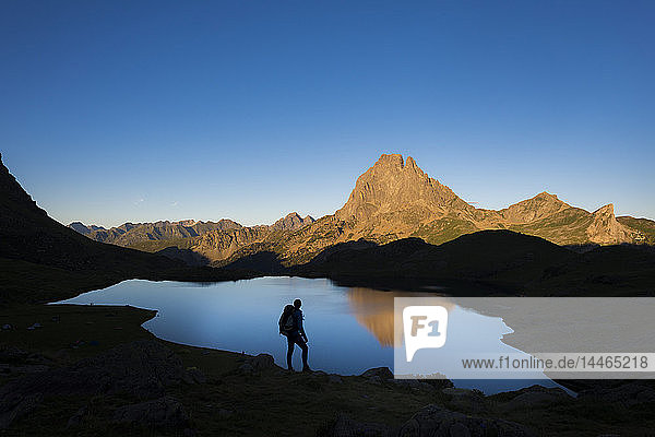 Taking in the view of Midi d'Ossau beyond Lac Gentau beside the GR10 trekking route in the French Pyrenees  Pyrenees Atlantiques  France