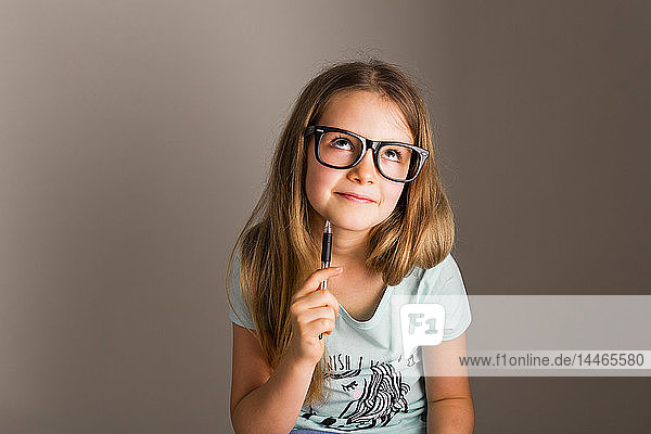 Portrait of smart girl with oversized glasses thinking