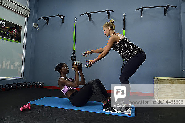 Two women doing fitness exercises with a ball in a gym