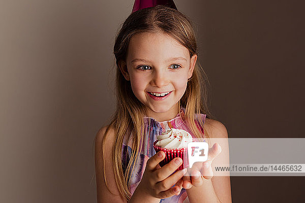 Portrait of happy little girl with cup cake