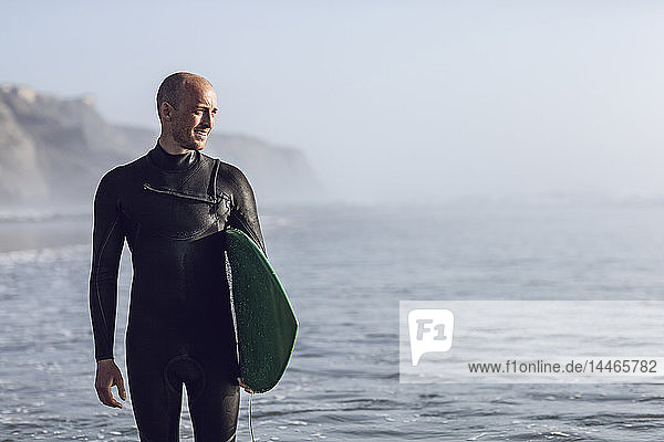 Surfer with surfboard wearing wetsuit looking at distance