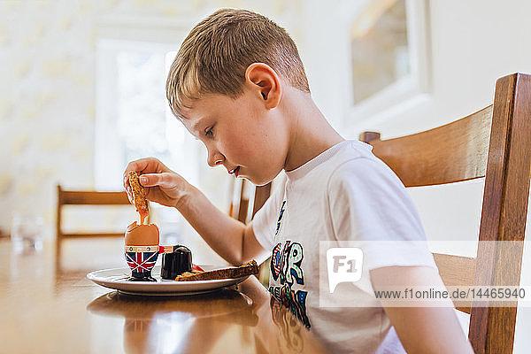 UK  sad boy sitting at breakfast table eating boiled egg