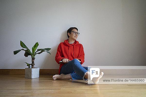 Junge Frau sitzt auf dem Boden und träumt vor sich hin