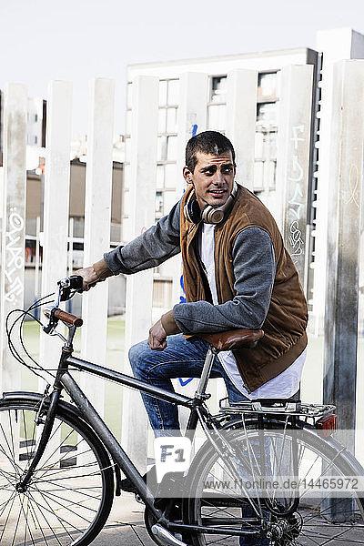 Junger Mann mit Fahrrad in der Stadt