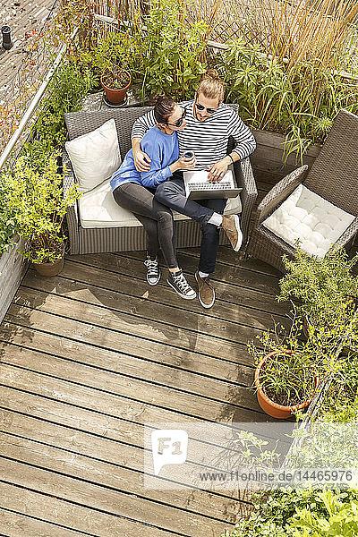 Junges Paar entspannt sich auf dem Balkon  sitzt auf der Couch und benutzt einen Laptop