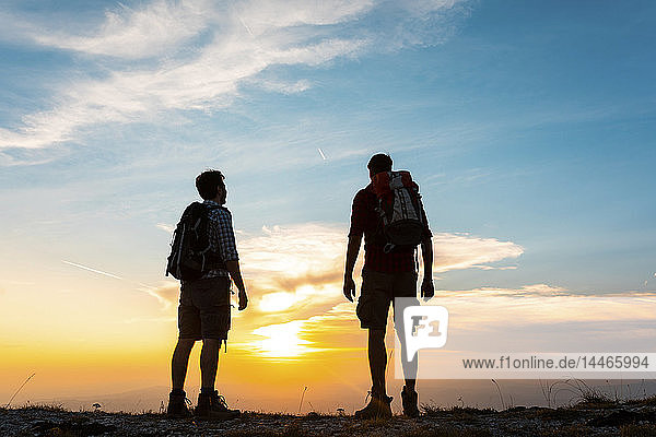 Italy  Monte Nerone  two hikers enjoying the view on top of a mountain at sunset