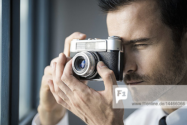 Close-up of businessman taking picture with vintage retro camera in front of office window