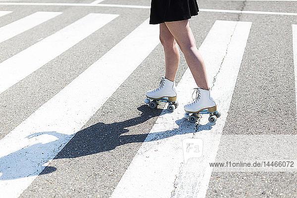 Junge Frau mit Rollschuhen auf Zebrastreifen  Teilansicht