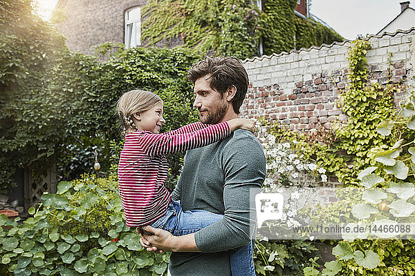 Father carrying daughter in garden of their home