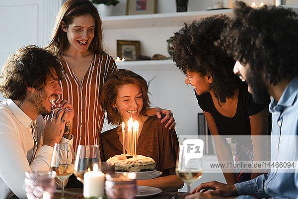 Freunde überraschen junge Frau mit einem Geburtstagskuchen mit brennenden Kerzen