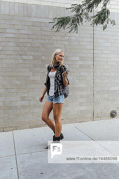Junge Frau mit Handy in der Stadt unterwegs