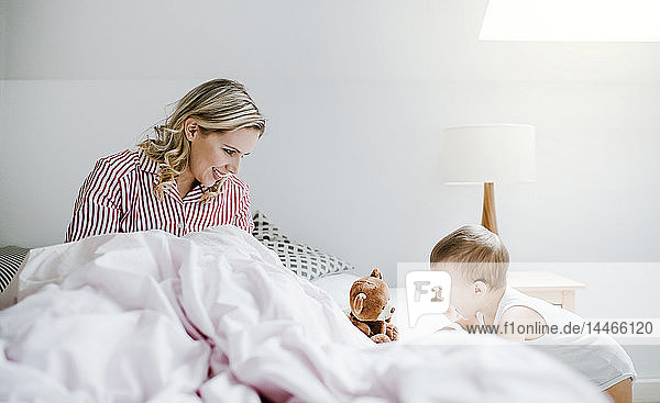 Smiling mother playing with toddler son in bed at home