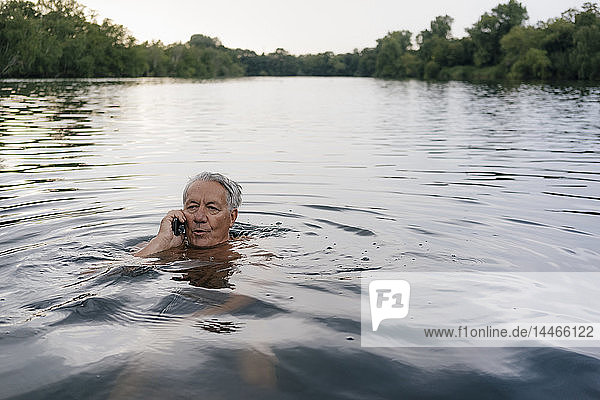 Senior man talking on cell phone in a lake