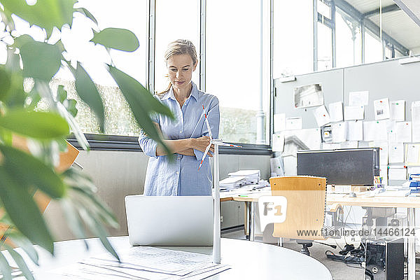 Frau im Büro mit Plan  Laptop und Windturbinenmodell auf dem Tisch