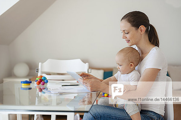 Mother and little daughter using tablet together at home