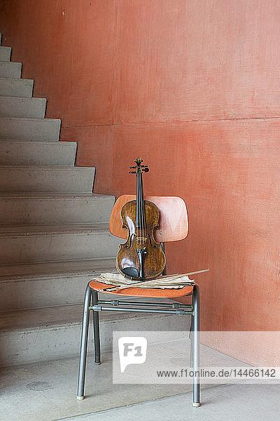 Geige  Bogen und Noten auf Holzstuhl im Treppenhaus