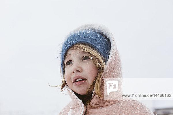 Portrait of little girl in snowfall