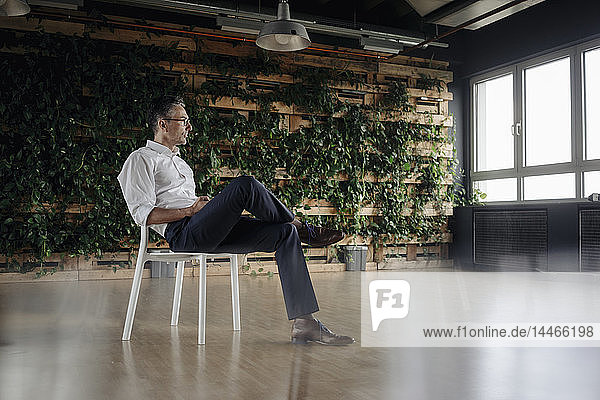 Geschäftsmann sitzt auf Stuhl im grünen Büro und denkt