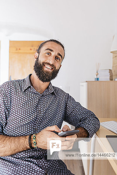Portrait of smiling young man using cell phone at home