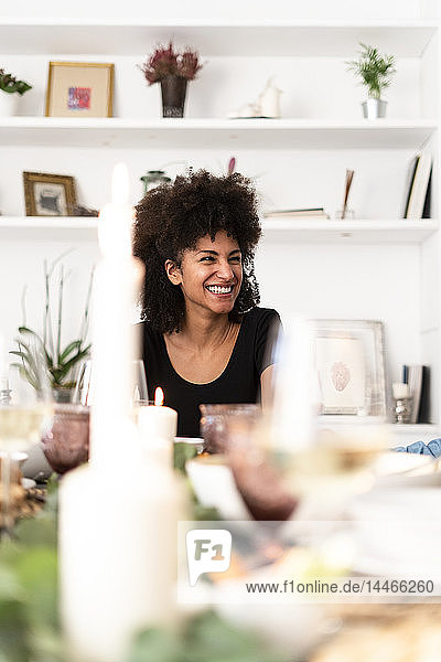 Porträt einer dunkelhaarigen Frau  die auf einer Dinnerparty sitzt