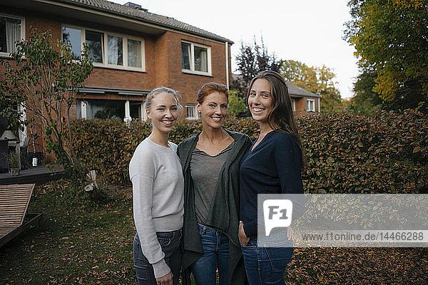 Porträt einer glücklichen Mutter mit zwei Teenager-Mädchen im Herbst im Garten