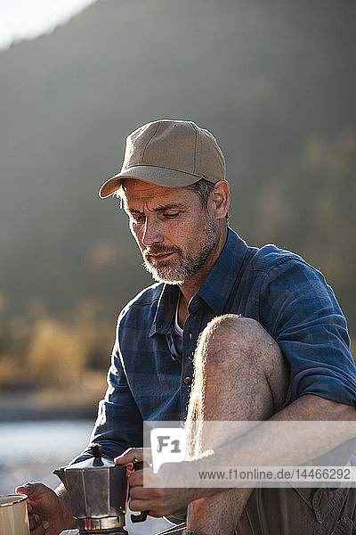 Mature man camping at riverside  using espresso machine